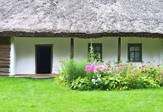 Flowerbed and ancient hut Royalty Free Stock Image