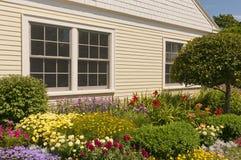 Flowerbeds ajardinados da casa foto de stock