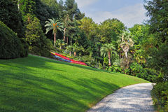 The flowerbeds, lawn and path. The flowerbeds, green grassy lawn and comfortable path in an exotic park. Lake Como, Villa Carlotta stock images