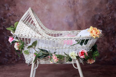 Flowered Baby Bassinet. White Wicker Flowered Baby Bassinet stock photos
