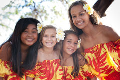Flowered Beautiful Polynesian Hula girls smiling at camera. Pretty Group of four Polynesian Hula girls smiling looking at camera in Friendship Royalty Free Stock Images