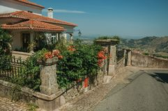 Flowered bushes in front of charming old house in Monsanto. Flowered bushes and stone wall with wrought iron fence in front of charming old house facade, on a stock images
