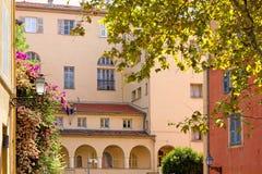 Flowered Courtyard among Elegant Buildings Stock Photography