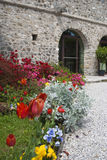 Flowered entrance. The entrance of a castle with a small garden on the way and some flowers plant on it Stock Photo