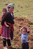 Flowered Hmong grandmother and her grand children. A Flowery Hmong grandmother and her grandchildren. It carries a child on her back, crossing her fingers. Able Royalty Free Stock Photos