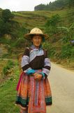 Flowered Hmong woman. Woman of the Hmong flowered market return. She wears a conical hat special region of North Vietnam Royalty Free Stock Photo