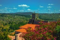 Flowered leafy trees and castle over rocky cliff. Flowered leafy trees and Castle on hilly landscape with wind turbines, in a sunny day at Sortelha. One of the stock image