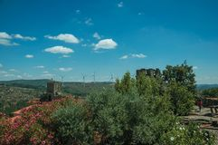 Flowered leafy trees and castle over rocky cliff. On hilly landscape with wind turbines, in a sunny day at Sortelha. One of the most astonishing and well stock images