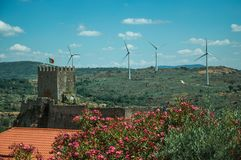 Flowered leafy trees and castle over rocky cliff. On hilly landscape with wind turbines, in a sunny day at Sortelha. One of the most astonishing and well royalty free stock photography