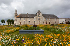 Flowered meadow with building. Antique hospital of Saintes , France ,with Flowered meadow in the forefront Royalty Free Stock Photography