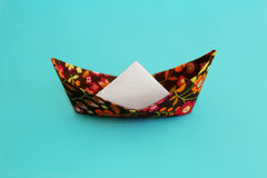 Flowered origami boat on blue solid surface Stock Photo