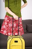 Flowered skirt woman ready to travel. Woman detail standing in front of a brown sofa with suitcase Stock Photography