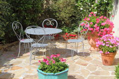 Flowered terrace with garden furniture. Flowered terrace with geranium in flowerpots and gray metal garden furniture during summer Stock Photo