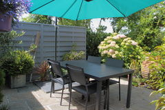 Flowered terrace with garden furniture. Flowered terrace with gray garden furniture and green sunshade Stock Image