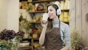 Flowergirl die aan muziek in grote hoofdtelefoons en het drinken koffie, camera luisteren beweegt zich van ver aan de close-upmen stock footage