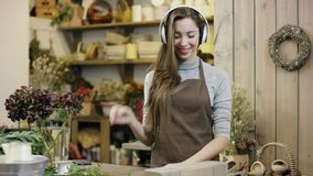 Flowergirl que escucha la música en auriculares grandes y que baila, en el extremo alguien para llamarla almacen de video