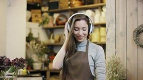 Flowergirl que escucha la música en auriculares grandes y que baila, movimientos de la cámara de lejos a la opinión del primer almacen de metraje de vídeo