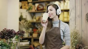 Flowergirl que escucha la música en los auriculares grandes y el café de consumición, movimientos de la cámara de lejos a la opin metrajes