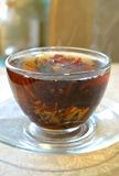 Flowering tea in the transparent cup on transparent saucer, the steam from the hot tea Stock Images