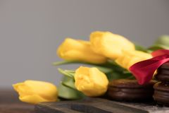 Flowering yellow tulips and chocolate biscuits, tied with satin red ribbon. A gift for your sweetheart. stock image