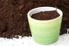 Flowerpot filled with soil by the pile of soil.  stock images