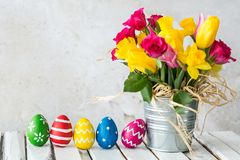 Flowerpot with flowers. Metal flowerpot with colorful flowers next to easter eggs royalty free stock photo