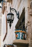 A flowerpot with a small plant decoration at window at narrow medieval street in Mdina, ancient capital of Malta, fortified. Medieval town. Popular touristic royalty free stock photography