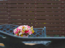 Flowerpot on vintage table and bench in garden and battens background. Flowerpot on vintage table and bench in outdoor garden and battens background, Copy Space stock photography