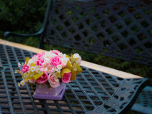 Flowerpot on vintage table and bench in outdoor garden and blurr. Y background, Low Key Stock Images