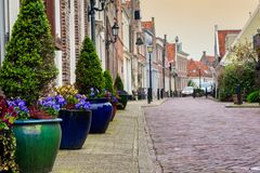 Flowerpots in Edam. Flowerpots on the street side in a small city Edam in Netherlands. Edam is a small village in the district Nordholland, Netherlands stock images
