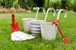 Flowerpots and garden hand tools. On the green grass stock photo