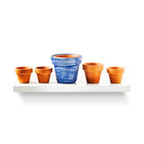 Flowerpots on shelf. Clay flower pots in a row on shelf isolated on white background. Garden equipment. Group of objects with clipping path Stock Photo