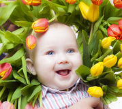 Flowerpower. Baby framed by colorful tulips Royalty Free Stock Images