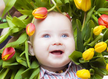 Flowerpower. Baby framed by colorful tulips Stock Photo