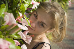 Flowers. The girl near to beautiful flowers in park Stock Image