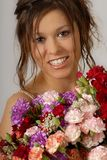With a flowers. European brunette model with beautiful smile holding flowers Royalty Free Stock Image