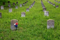 Flowers Adorn Civil War Gravestone. A patriotic bouquet of red, white and blue flowers adorns a Civil War grave in the U.S. National Cemetery in Vicksburg Stock Photography