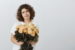 Flowers, again, how boring. Portrait of unimpressed unsatisfied attractive female with curly hair, holding beautiful. Bucket of roses, expressing Stock Image