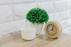 Flowers and alarm clock on a wooden table Stock Image
