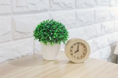 Flowers and alarm clock on a wooden table Royalty Free Stock Photo