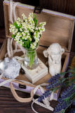 Flowers and angel decor composition. Lily of the Valley and lavender flovers, and angel figure jn the brown wood table Stock Photo