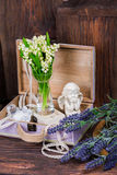 Flowers and angel decor composition. Lily of the Valley and lavender flovers, and angel figure jn the brown wood table Stock Photography
