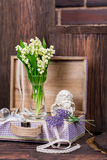 Flowers and angel decor composition. Lily of the Valley and lavender flovers, and angel figure jn the brown wood table Royalty Free Stock Images