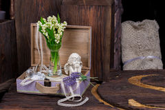 Flowers and angel decor composition. Lily of the Valley and lavender flovers, and angel figure jn the brown wood table Stock Image