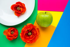 Flowers and apple on colorful background. Apple and flowers on bright background stock photo