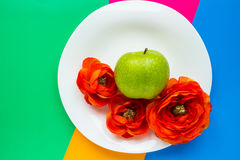 Flowers and apple on colorful background. Apple and flowers on bright background stock photography