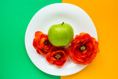 Flowers and apple on colorful background. Apple and flowers on bright background royalty free stock photography