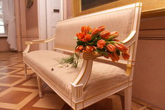 Flowers On Arm Chair. Bouquet of orange/red tulips resting on the arm of a bench seat in a home setting Royalty Free Stock Images