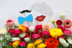 Flowers arrangement, paper fake lips, tiara and mustache in sticks. Top view of beautiful flowers arrangement, paper fake lips, tiara and mustache in sticks in stock photo