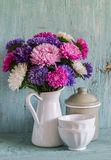 Flowers asters in a white enameled pitcher and vintage crockery - ceramic bowl and enameled jar, on a blue wooden background. Royalty Free Stock Images
